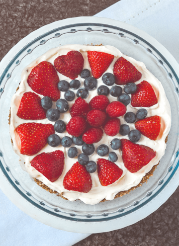 [image is a view of a keto lemon berry tart from the top. Strawberries, raspberries and blueberries form a decorative circular pattern on top of a white filling]
