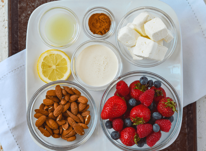 [image of several different sized bowls filled with ingredients on a plate for the keto lemon berry tart. The ingredients shown are lemon juice, cinnamon, cream cheese, cream, almonds, and strawberries