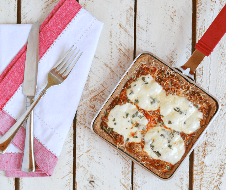 Image of Keto personal pan pizza in a pan next to a napkin with a knife and fork on top