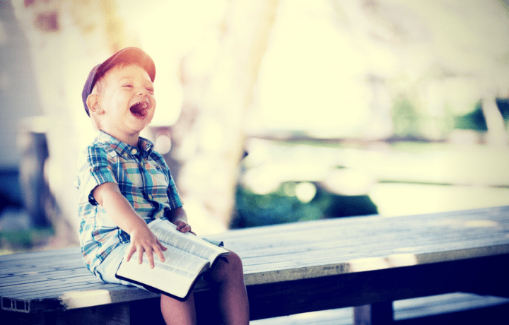 image of a boy laughing, holding a book on his lap, sitting on a bench