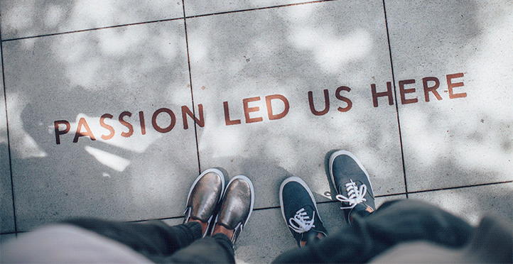 "image of two pairs of feet on the side walk. Text reads ""passion led us here""."