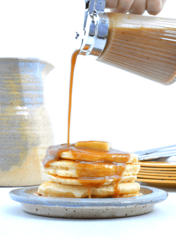 Image of a plate of pancakes with keto buttery maple syrup being poured onto them.