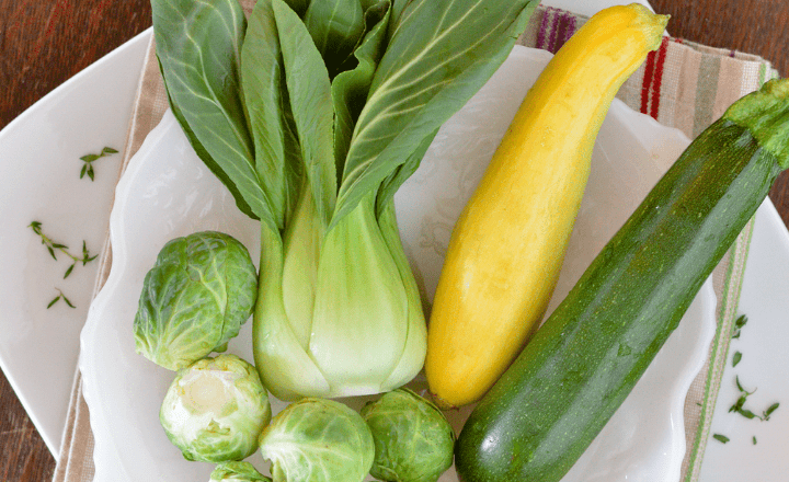 Image of fresh brussels sprouts,Baby bok choy, and green and yellow zucchini on a plate