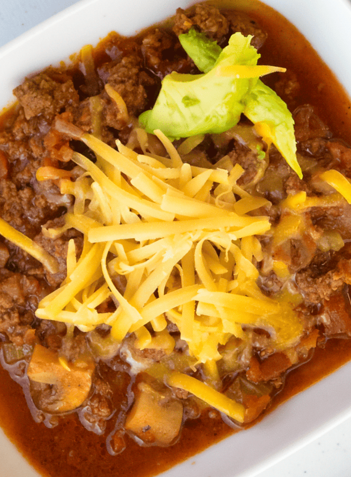 Image of a white bowl with Keto instant pot southwestern chili topped with cheddar cheese and avocado slices