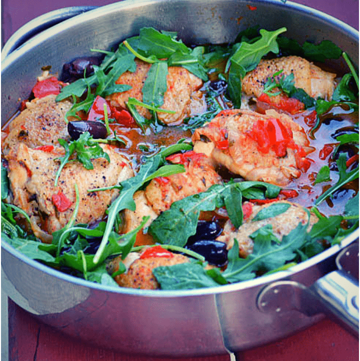 Image of a pan with chicken, tomatoes, olives and arugula inside it.