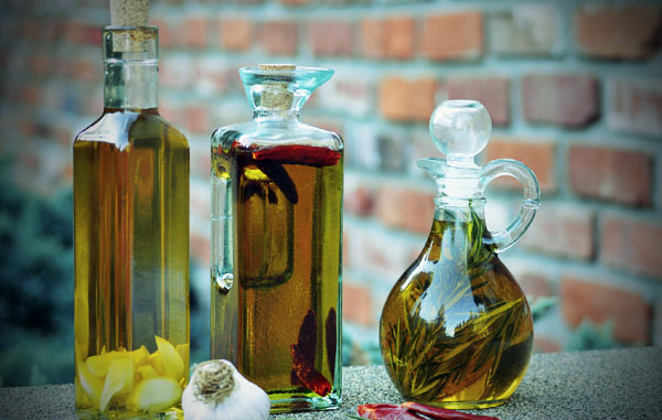 3 bottles that contain olive oil, garlic, dried chili peppers and dried rosemary.
