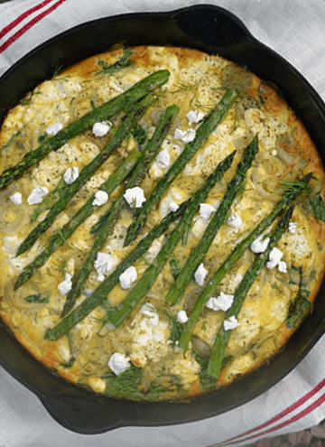 image of a black cast iron pan with goat cheese and asparagus quiche inside