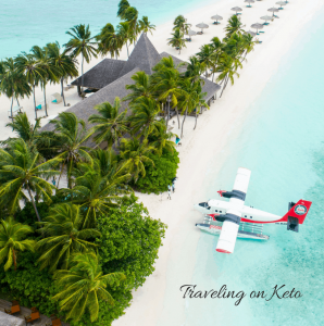 image on a tropical beach with an airplane parked on the beach next to tropical trees and beach houses.