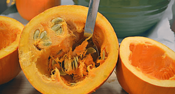 image of a pumpkin cut in half with the seeds being scraped out.