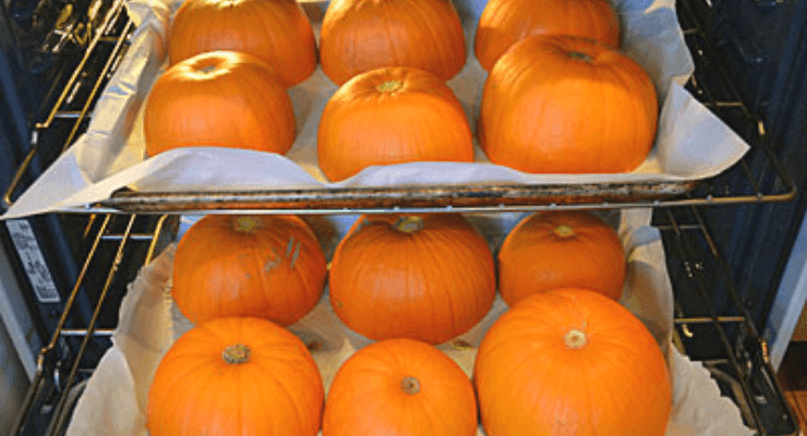 Image of pumpkins cut in half on trays in the oven